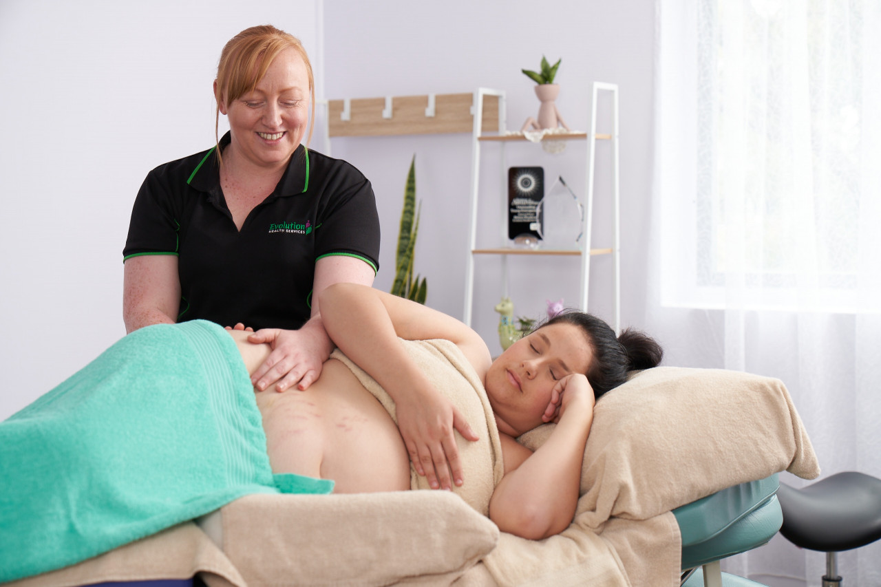 Woman laying on her side with supportive pillows while receiving a pregnancy massage from a qualified massage therapist