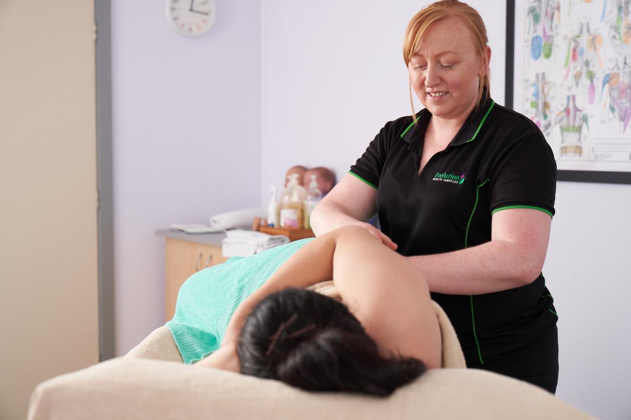 Woman laying on massage table with qualified post natal massage therapist providing massage