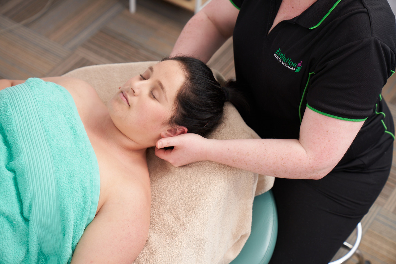 Woman laying on massage table receiving pregnancy massage to neck by qualified massage therapist