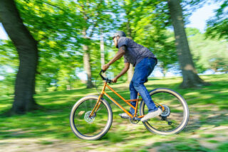 Rider taking a Marin Larkspur 2 through a wooded park.