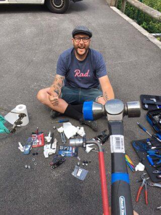 John Oldale sat on floor fixing a bike