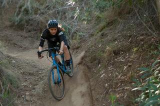 Female rider on gravel bike on dusty trail
