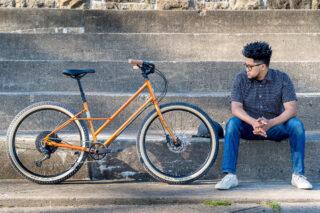 Man sitting on stairs, next to a Marin Larkspur 2 bike.