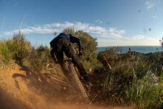 Marin's Matt Cipes, kicking up gravel, riding a mountain bike in Italy.