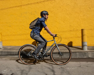 Man riding bike in urban environment with yellow wall