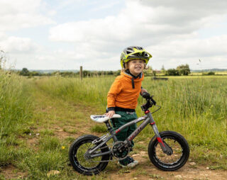 Young boy smiling in yellow Troy Lee Designs helmet on kids mountain bike