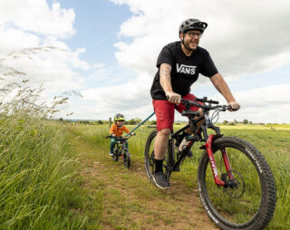 Father and son ride mountain bike with Kids Ride Shotgun TowRope