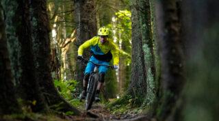 Nikki Whiles riding a Rift Zone Carbon 2 mountain bike through the trees, Wales UK.