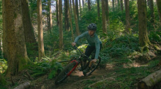 Rider cornering on a trail through the woods on a Marin El Roy mountain bike.
