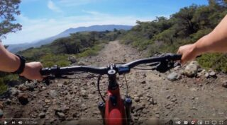 Point-of-view shot of rider on a Marin Alpine Trail E1 bike, climbing a rough fire road.
