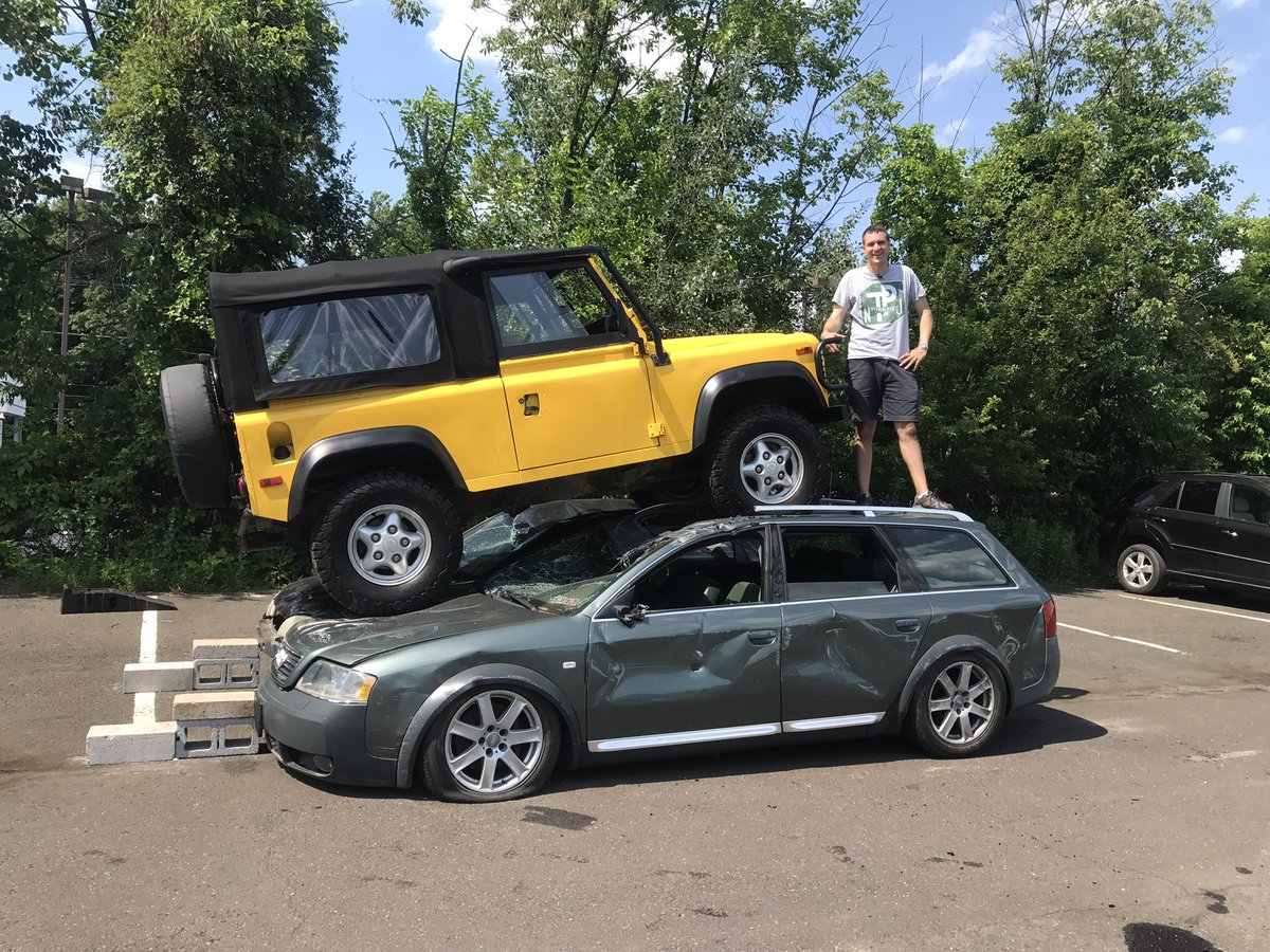 Image of Doug DeMuro with a yellow Land Rover Defender and green Audi.