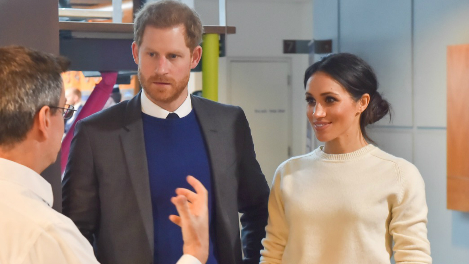 Prince Harry and Meghan Markle talking to a man at a science clinic on a Royal visit