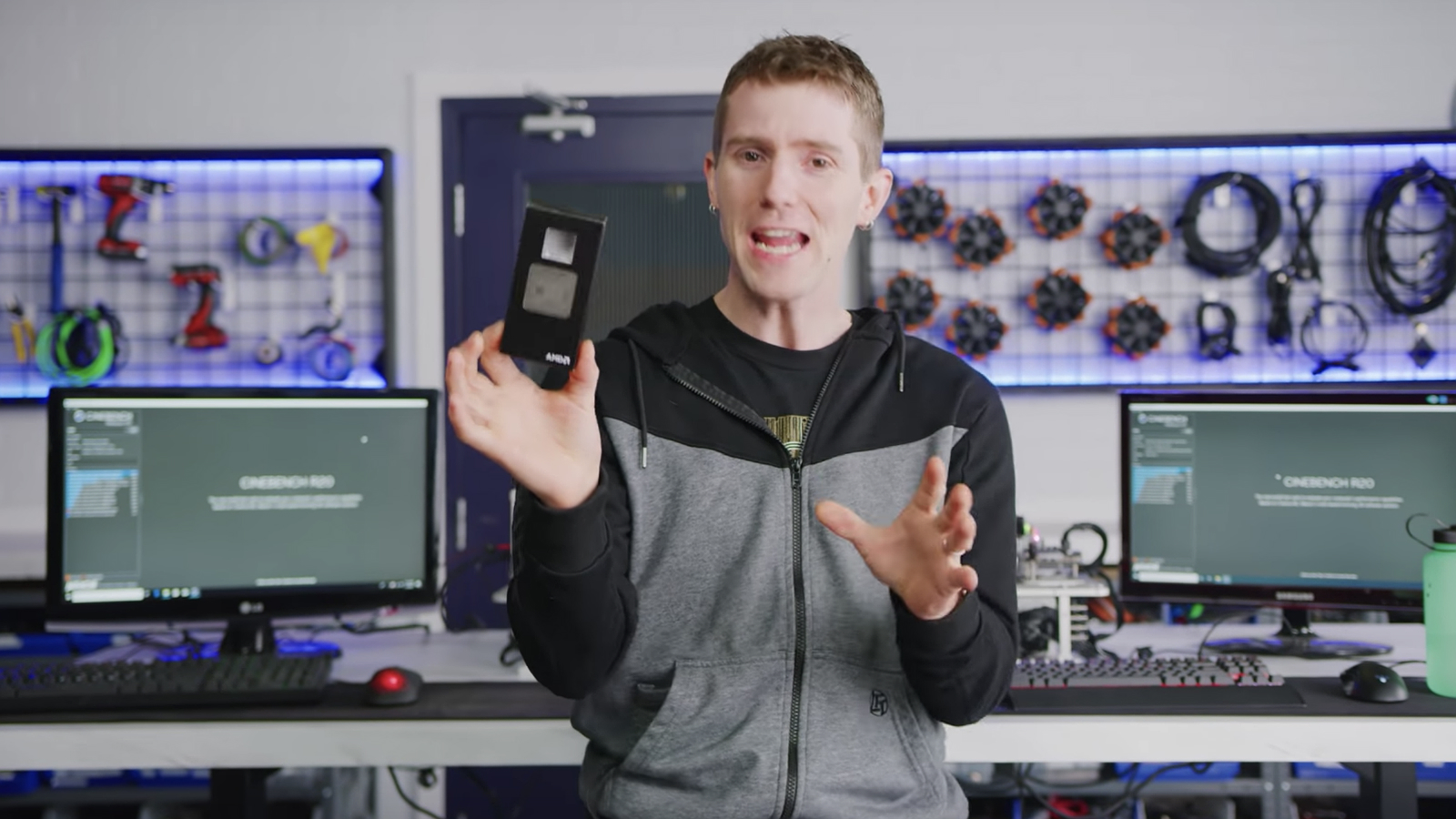 Linus holds a GPU in his hand in office with two monitors behind him