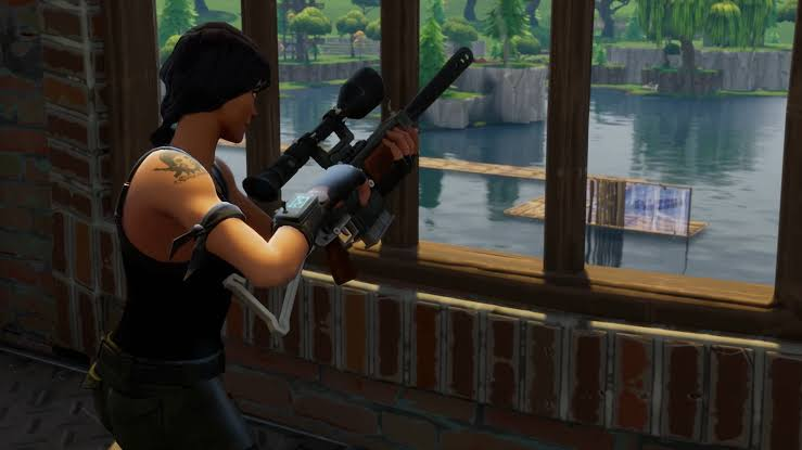 Fortnite sniper patiently waiting indoors.