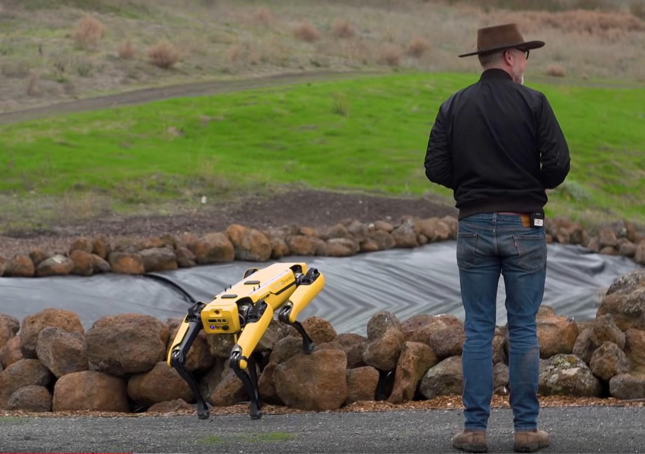 Adam Savage standing outside with the Boston Dynamics robot dog.