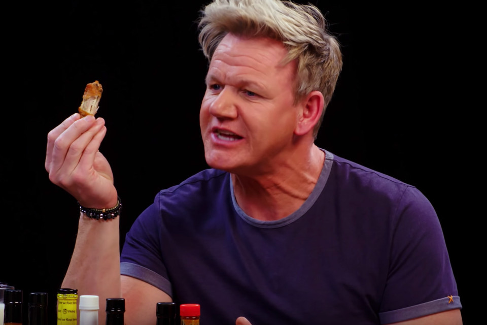 Gordon Ramsey eating a chicken wing on Hot Ones.