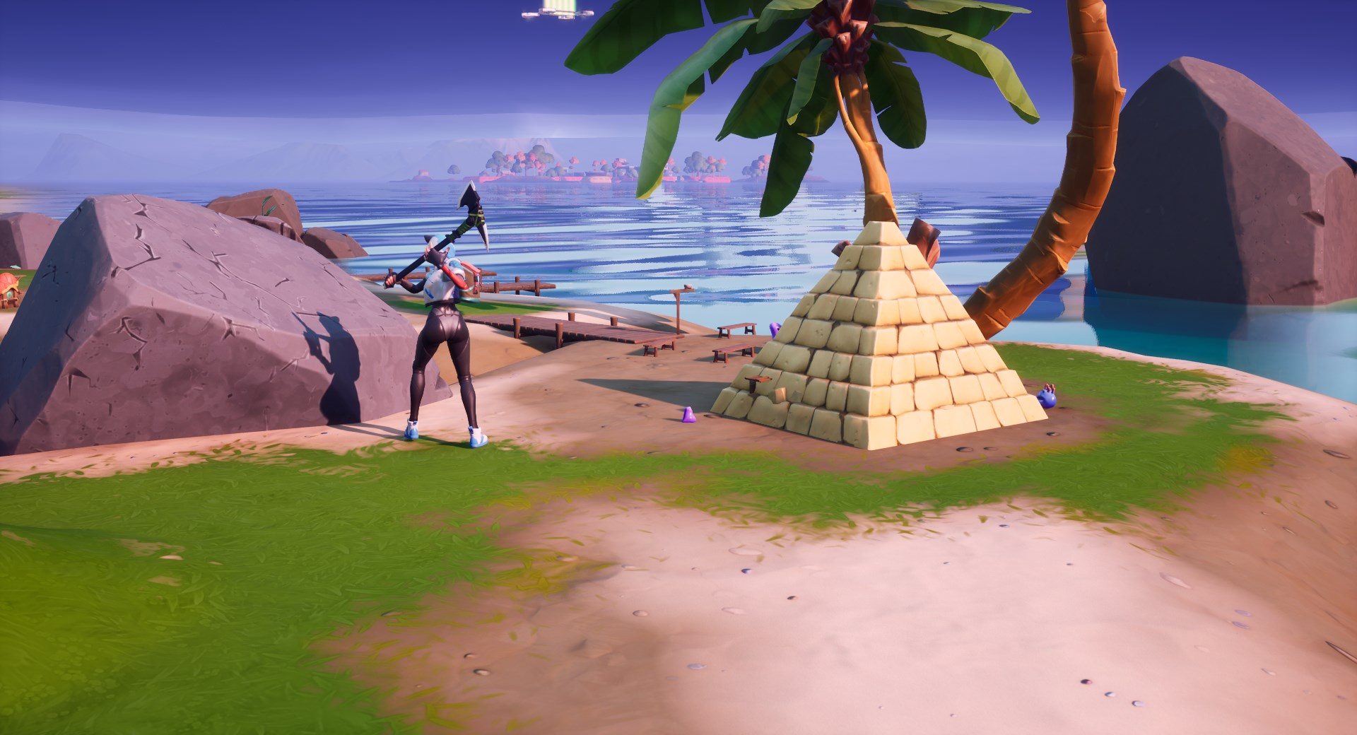 A Fortnite player breaking stone beside the Coral Buddies' pyramid.