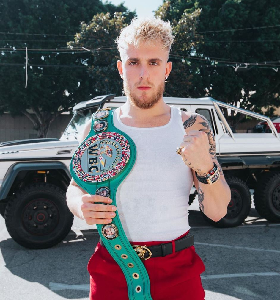 Jake Paul poses with a boxing championship belt.