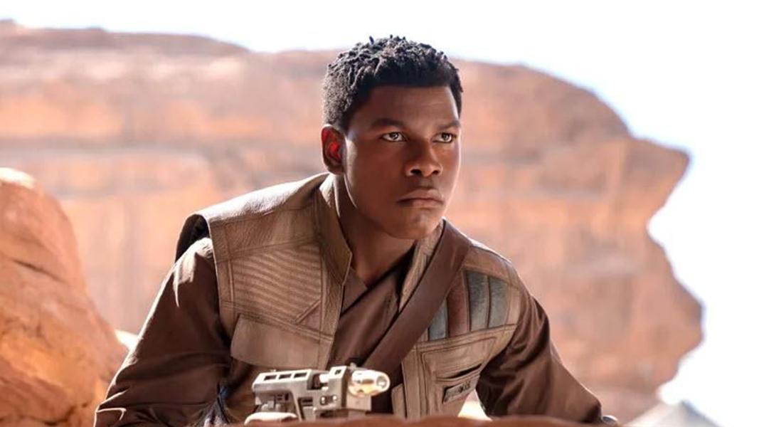 Finn holding a blaster in star wars