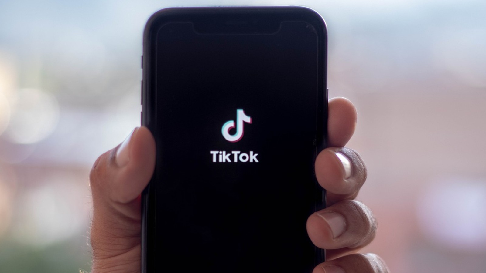 The TikTok launch screen phone held by a hand