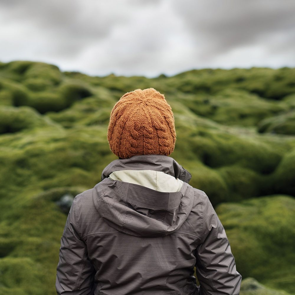 person facing away from the camera looking at a green hill in the distance