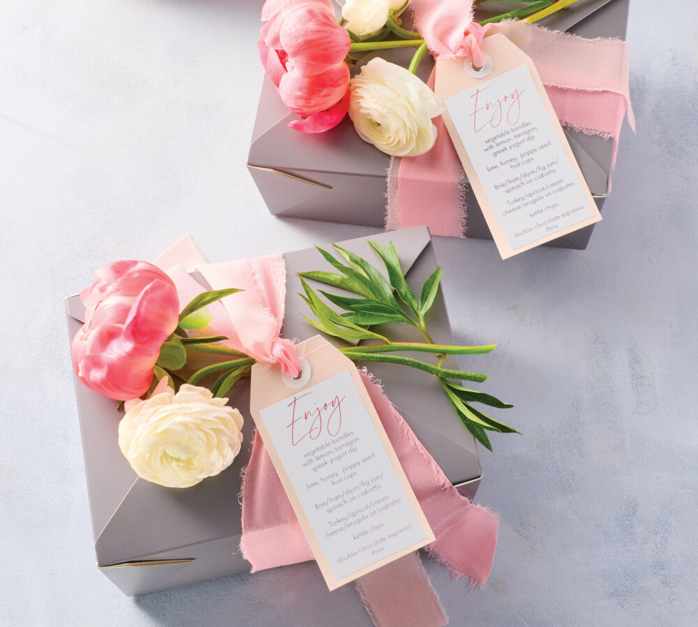 Two boxed lunches with tags fixed with ribbon