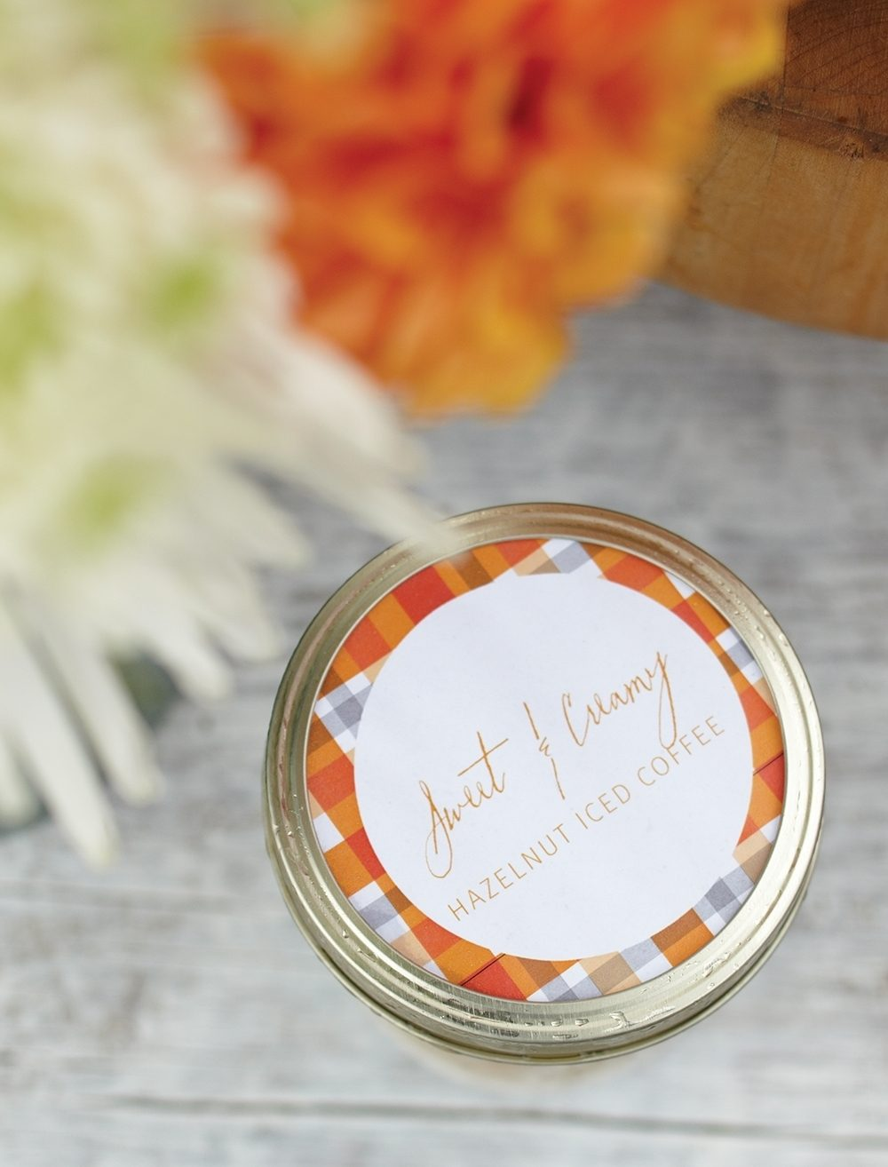 Canning jars with labels identify cold drinks at a casual outdoor fall party.