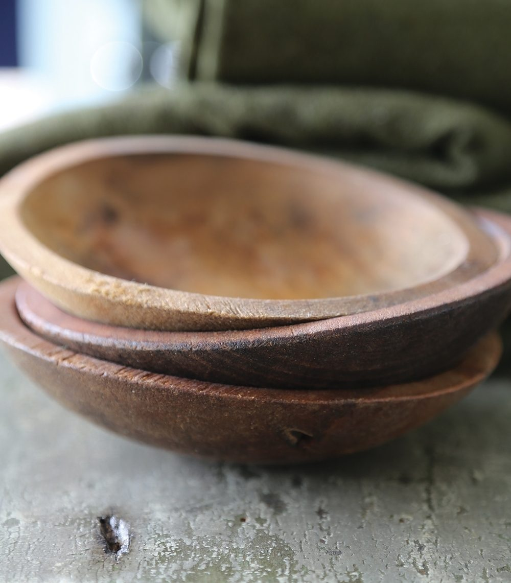 wooden bowls sit in front of a wool blanket