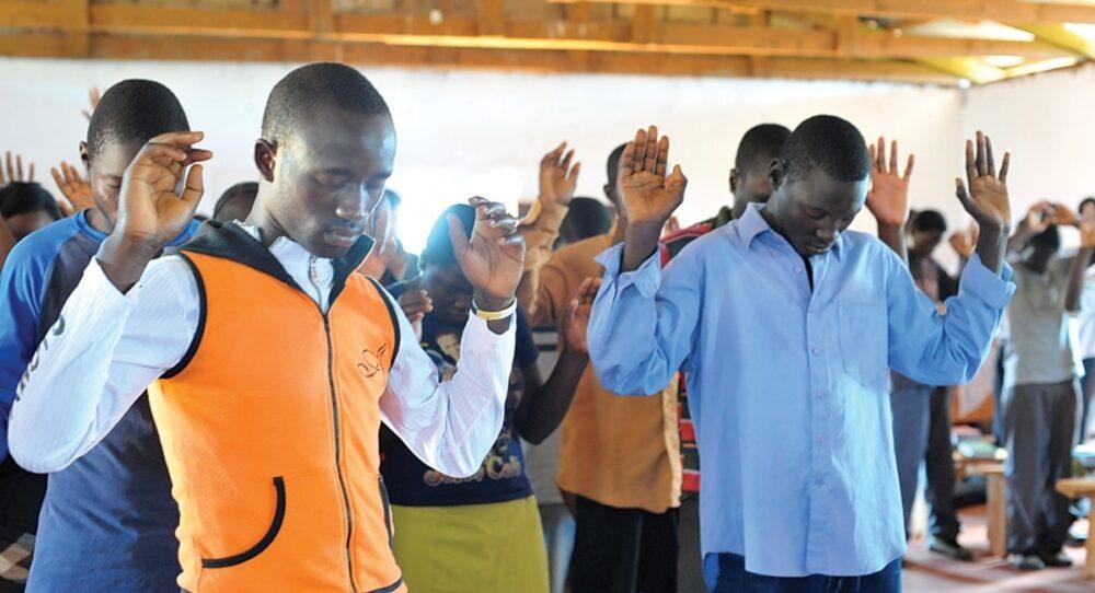Men pray in Chishiko, Zambia