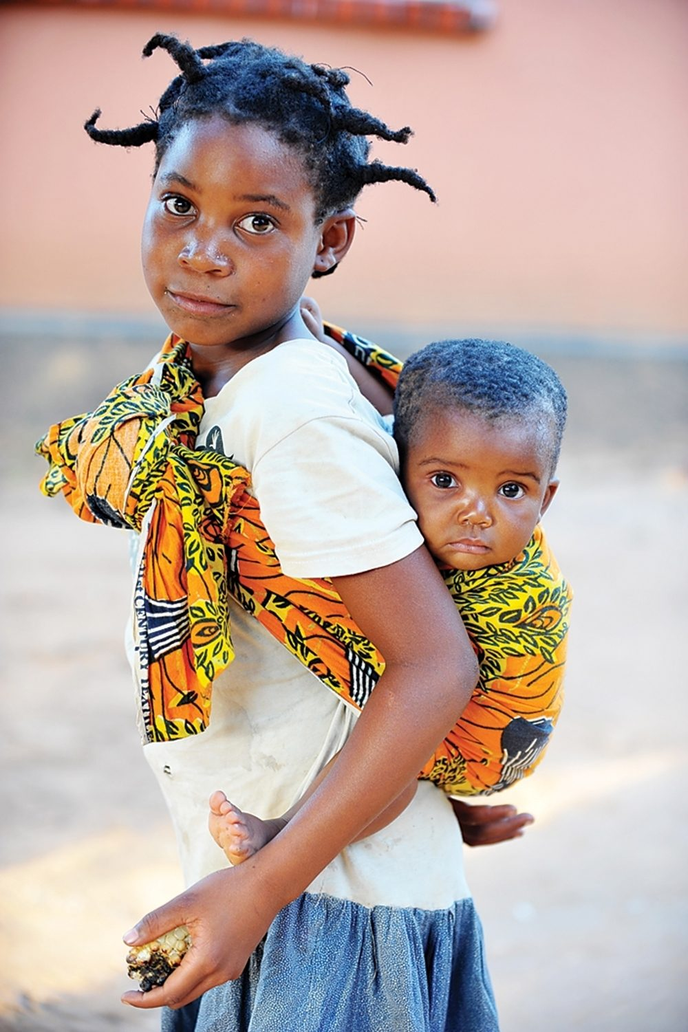 A Zambian girl carries a baby in a brightly-colored sling.