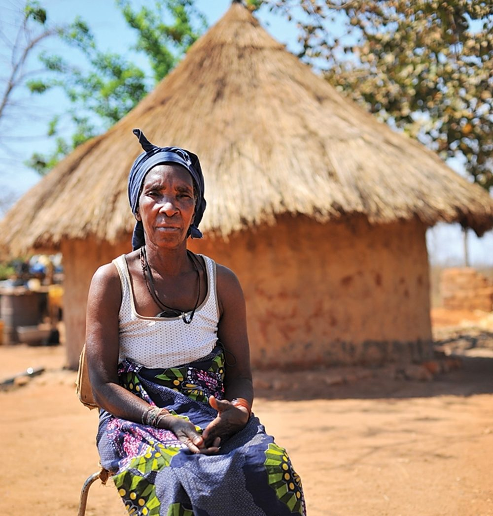 A Zambian woman sits in front of a thatched-roof hut.