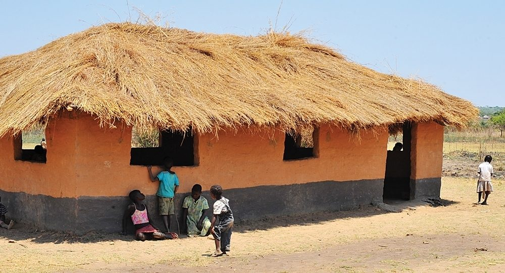Children congregate outside the thatched-roof structure that serves as a school for 120 students in Chishiko, Zambia.