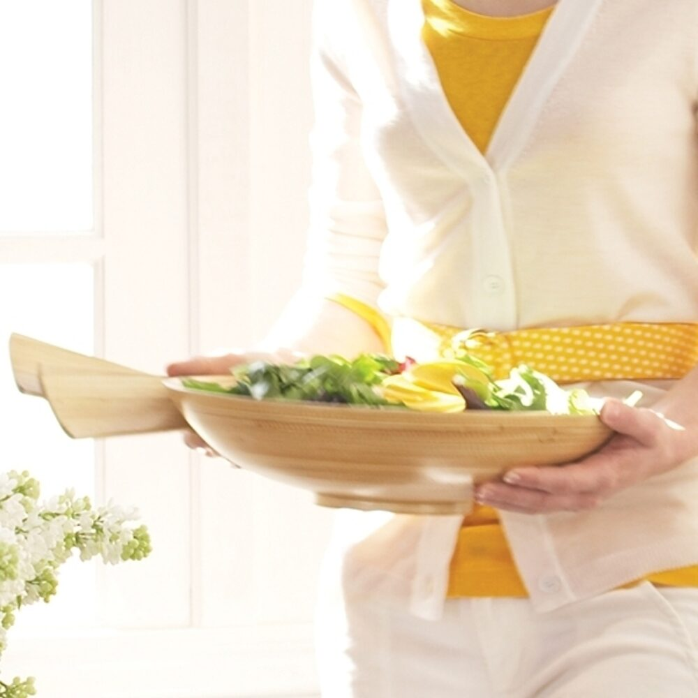 A woman carries a wooden salad bowl and tongs.