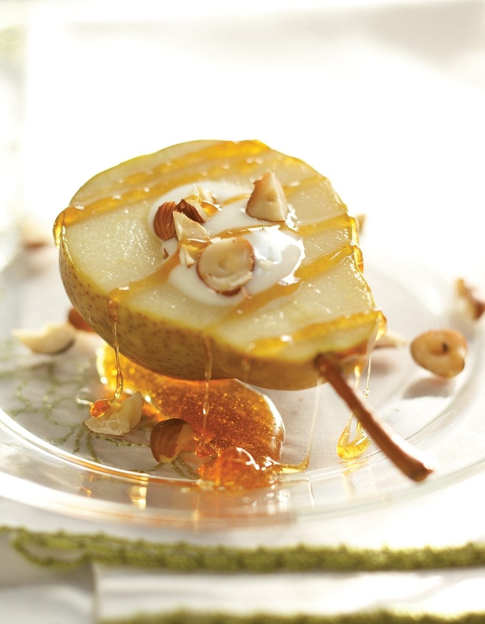 A cored pear-softened after simmering on a cooktop-serves as a miniature bowl for vanilla yogurt and chopped hazelnuts. Ginger sauce sweetened with agave is drizzled over the fruit.