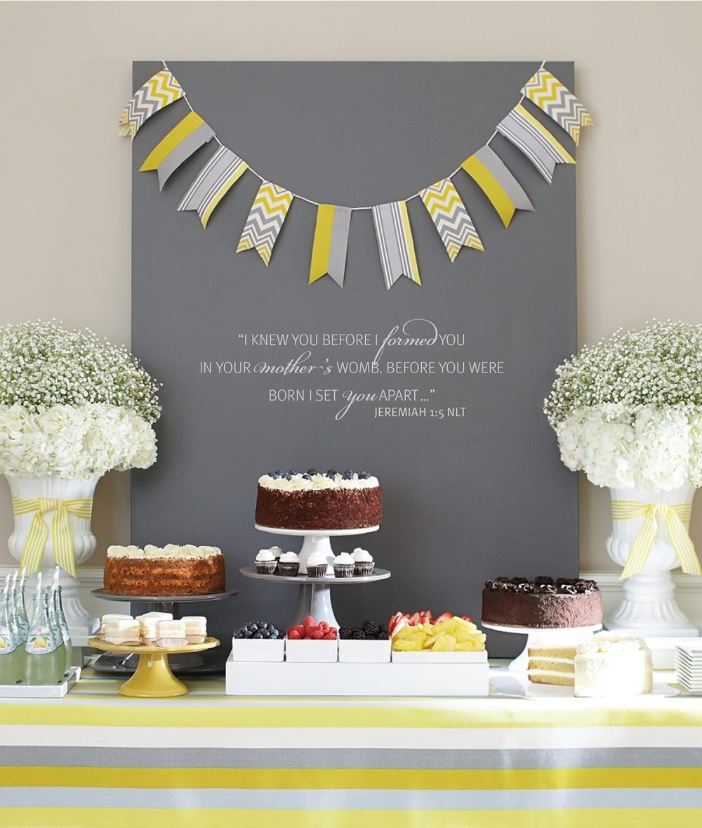 A spread of cakes, fruits and beverages and the Bible verse Jeremiah 1:15 is set for a yellow-and-gray-themed co-ed baby shower