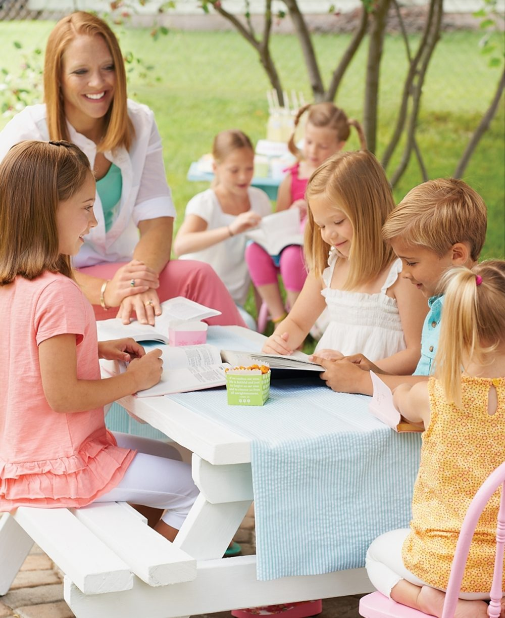 Children gather around an outdoor table for a summer Bible club.