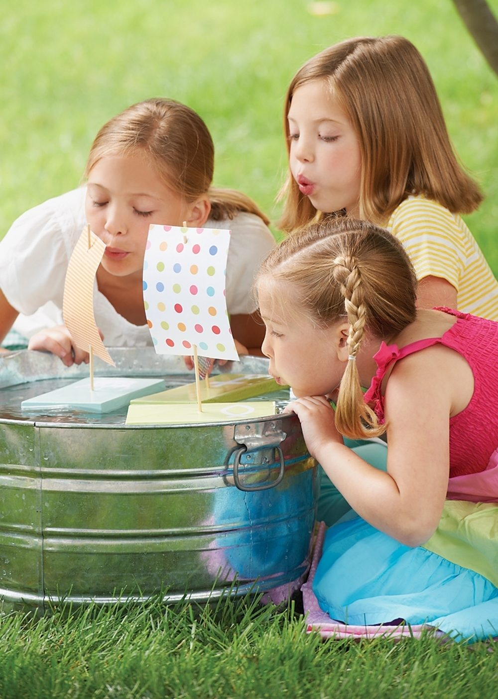 Three girls move their homemade sailboats across a tub of water.