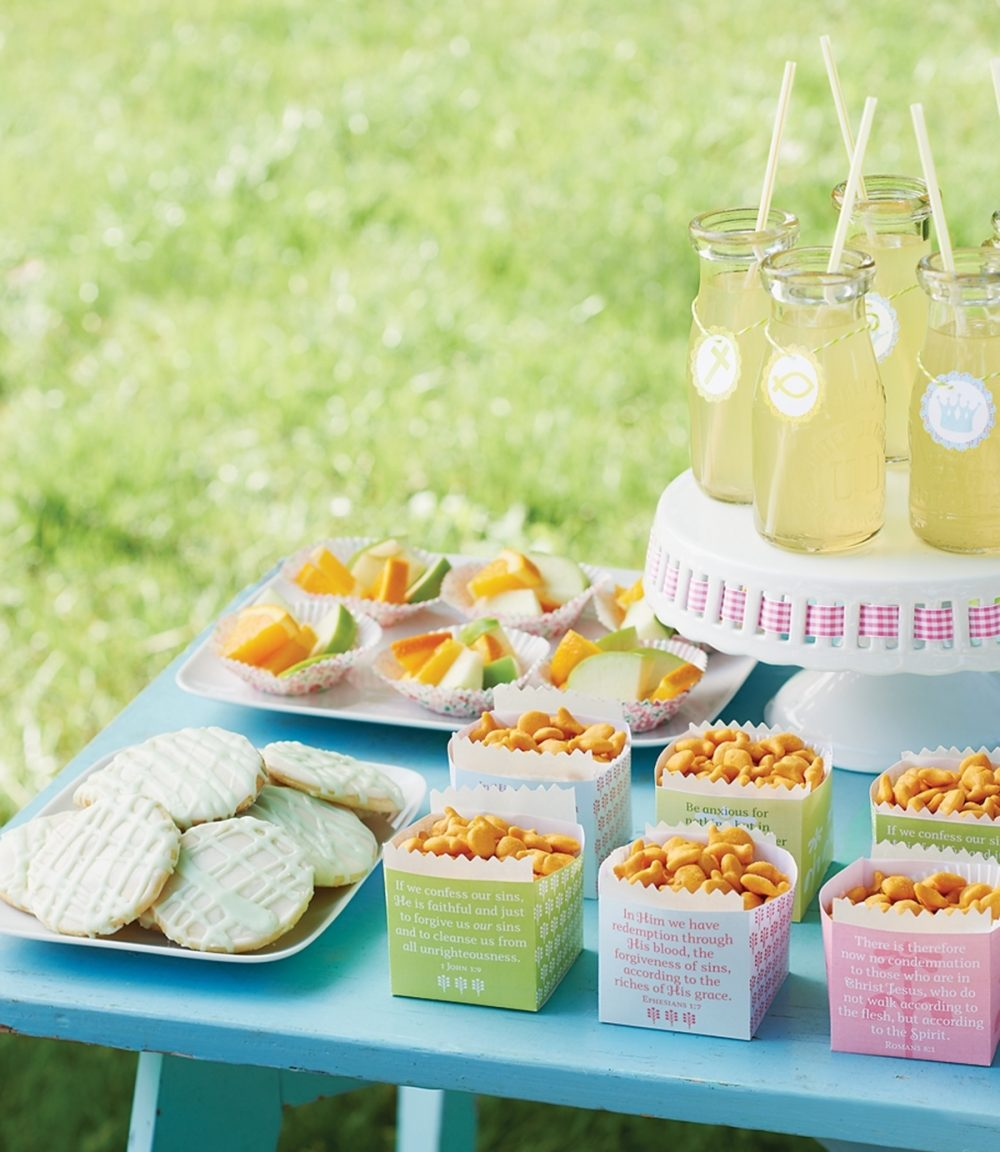 Snacks are served on a table for a backyard Bible club in containers with Bible verses and Christian symbols.