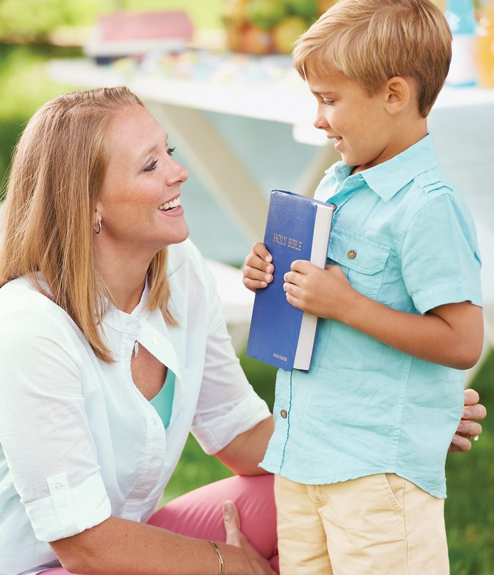 A small boy holds a Bible with the adult leader of a backyard Bible club.