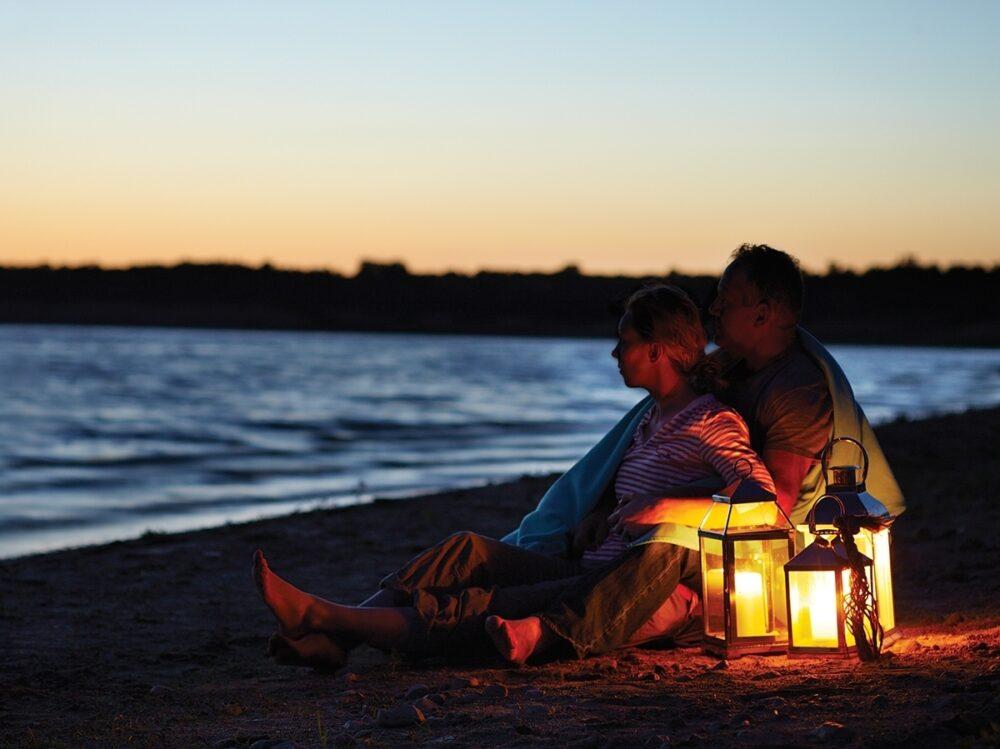 A couple sits on a beach illuminated by lanterns.