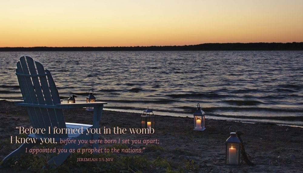 An Adirondack chair sits among lanterns on a beach with the Bible verse Jeremiah 1:5