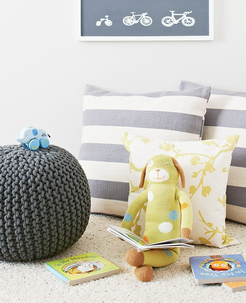 A reading nook in a baby's nursery is outfitted with pillows, a knitted pouf, a stuffed dog and books.