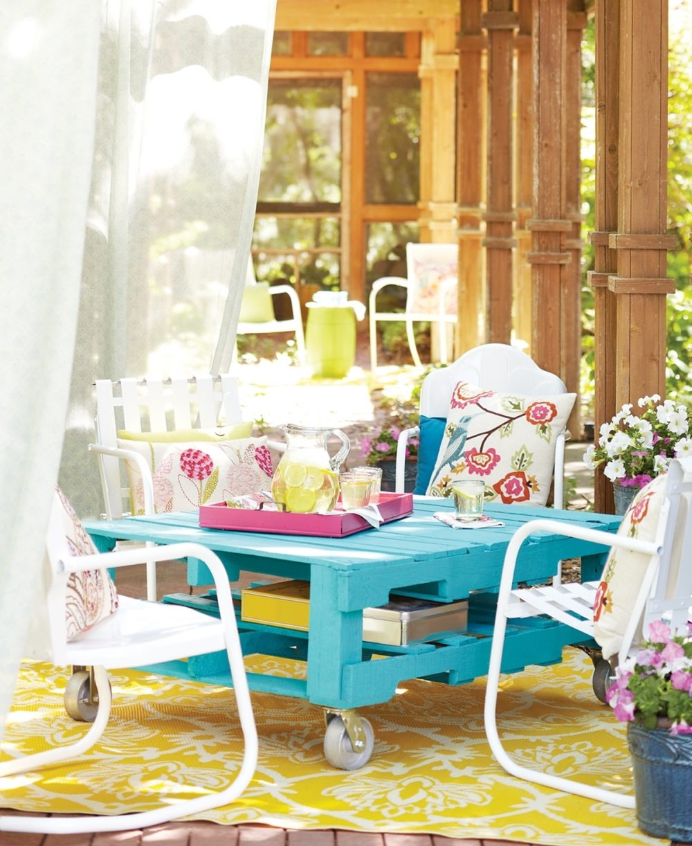 Chairs surround a bright outdoor table made from a pallet.