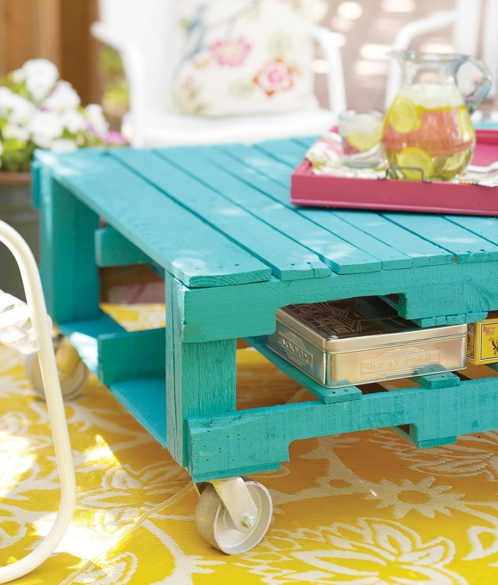 A bright turquoise table built from pallets rolls wherever it's needed outside.