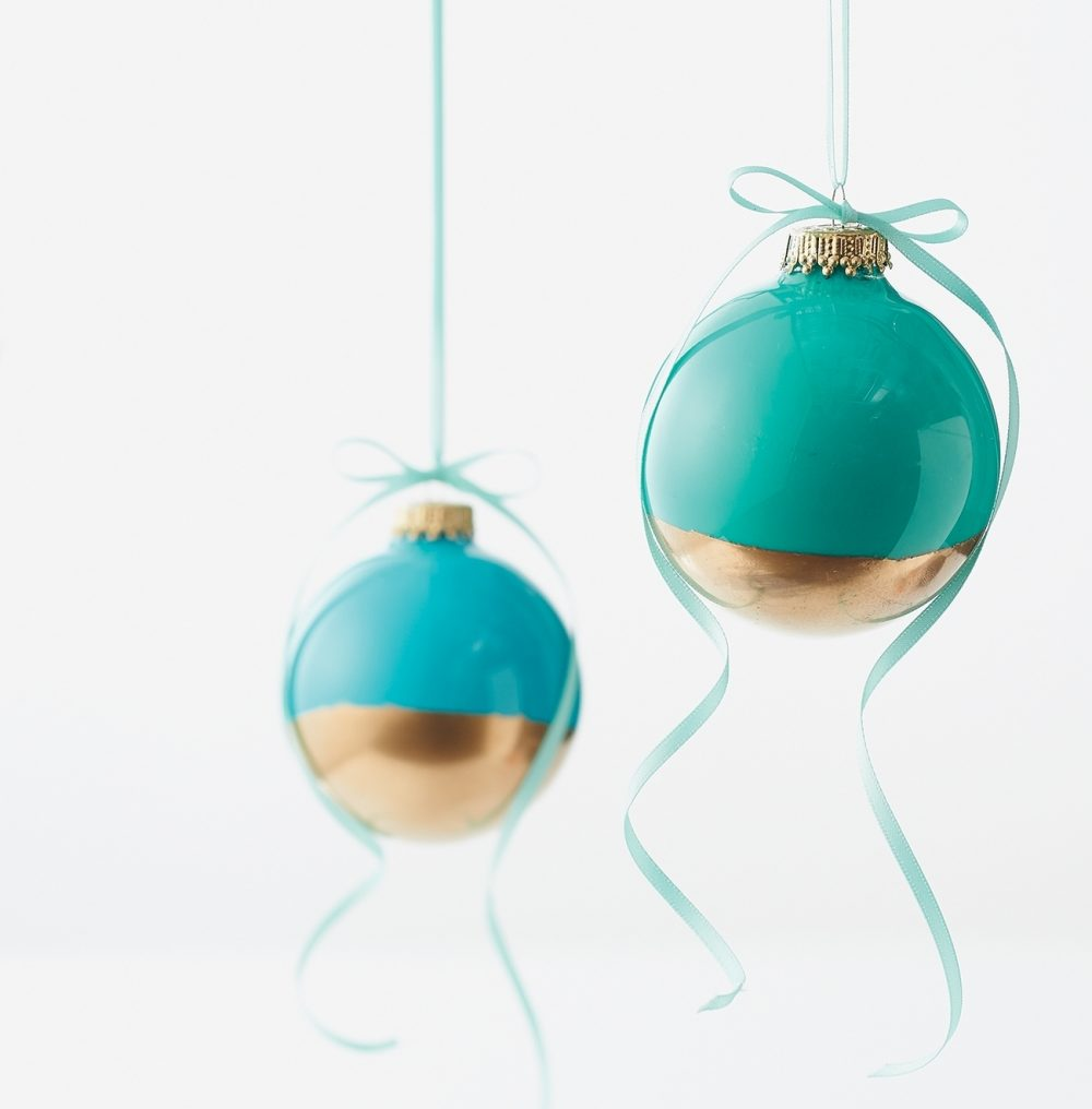 Color-dipped ornaments: Glass paint and spray paint embellish plain glass balls with color and shine. Add satin ribbon to these tree decorations. Gift one or nest a collection in a pretty box filled with shredded paper.