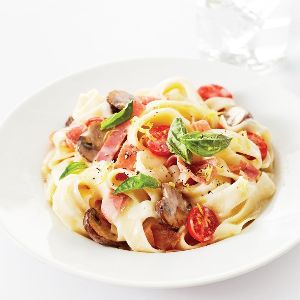 Steaming bowls of Prosciutto and Mushroom Fettuccine serve as the perfect foundation for a satisfying meal.