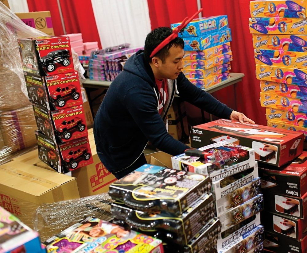 An unemployed father searches through stacks of toys, looking for Christmas gifts for his children. Donations and financial assistance provided by local branches of The Salvation Army make it possible for needy families to enjoy the holidays.