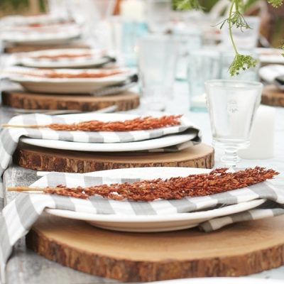 Slabs from tree trunks make rustic chargers, while dish towel napkins and mismatched dinnerware keep an outdoor fall party simple and inexpensive.