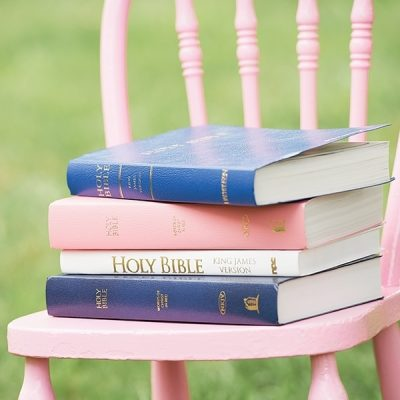 A stack of Bibles rests on a child's pink chair.
