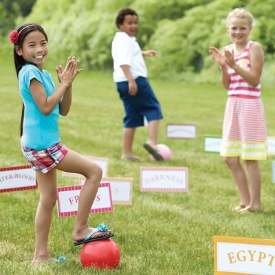 Three children play a game of Moses' Kickball Croquet outside.